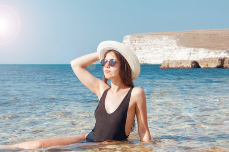 Beautiful girl in bikini, glasses and hat in clear sea water Stok Fotoğraf