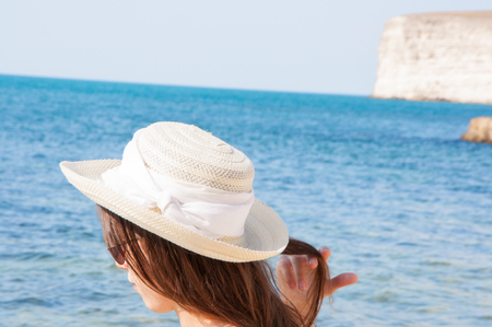 Beautiful girl in sunglasses and hat against the sea Stok Fotoğraf