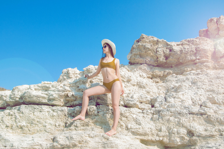 Beautiful girl in a bikini, hat and sunglasses sunbathing on the background of white rocks