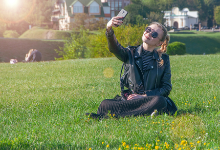 A beautiful blonde girl sitting on a green lawn and makes selfie Stok Fotoğraf