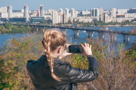 A beautiful blonde girl making photos of the city on a smartphone Stok Fotoğraf