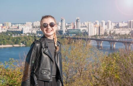 A beautiful blonde girl stands on the background of the city and smiles Stok Fotoğraf