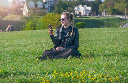 A beautiful blonde girl sits on a green lawn and looks in a smartphone