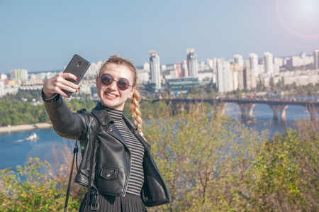 A beautiful blonde girl stands on the background of the city and makes selfie