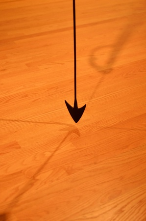 pendulum: Arrow pendulum over wooden floor Stock Photo