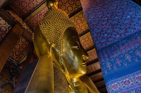 reclining: Gold Reclining Buddha at Wat Pho, Bangkok, Thailand.