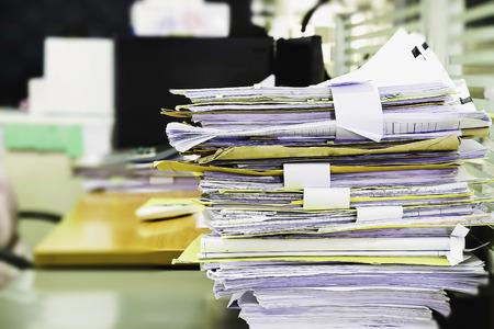 オフィスの机、ビジネス用紙上未完成書類の山