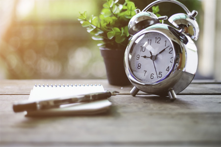 Time management concept: alarm clock, pen and notepad on old wooden table