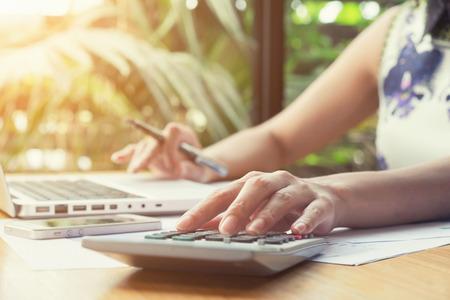 femme d & # 39 ; affaires asiatique en utilisant une calculatrice pour calculer le ton vintage tone