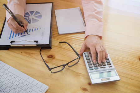 Asian Business woman using a calculator to calculate the numbers vintage tone