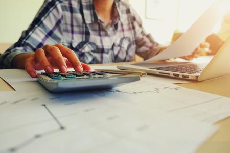 Asiatische Geschäftsfrau , die einen Taschenrechner verwendet , um die Zahlen zu erzielen