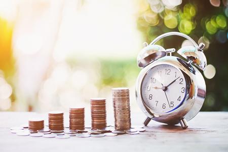 グリーンボケの背景、ビジネスファイナンスとマネーコンセプト、将来の準備のためにお金を節約.時間のお金の概念で時間とお金のクローズアップ