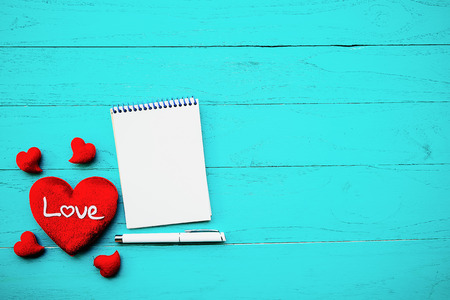 Red heart and notebook on wooden.Valentine day