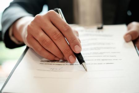 Agente de bienes raíces con mano poniendo la firma del contrato, tener un contrato en vigor para protegerlo, firma de acuerdos modestos en la oficina. Concepto de bienes raíces, mudanza o alquiler de propiedad.