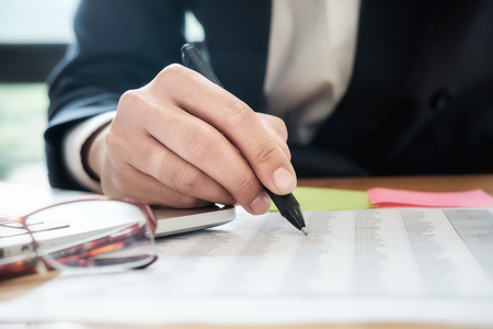 La gente de negocios que se reúne para trabajar con un nuevo proyecto de inicio utiliza notas de publicación para compartir tablas y gráficos de datos de análisis y discusión de ideas.