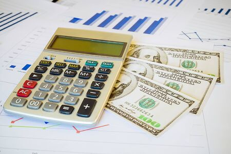 calculator and money on business financial report. Accounting