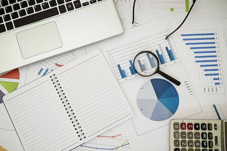 Magnifier calculator and notebook on Business report financial accounting graphs analysis