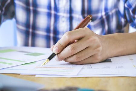 Close up Human Hand Signing contract on Formal Paper at the Table Stock Photo