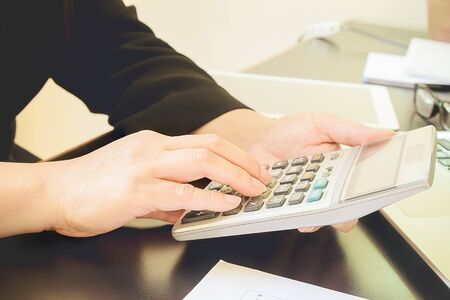 Asian Business woman using a calculator to calculate the numbers Archivio Fotografico