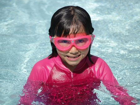 A little girl enjoys summer in the pool.