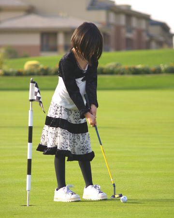 A young girl has fun playing golf on a beautiful green. 版權商用圖片