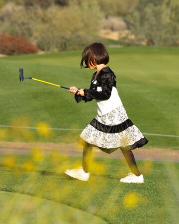 A young girl has fun playing golf on a beautiful green. Imagens - 4940783