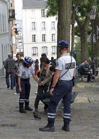 PARIS, FRANCE - JULY 2011 - Two young Roma women are questioned and searched by French police after being suspected of theft in Montmartre. Recently, the French government has carcked down on some of the Roma population due to crimes involving theft and e Stock Photo - 11867477