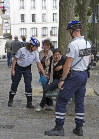 PARIS, FRANCE - JULY 2011 - Two young Roma women are questioned and searched by French police after being suspected of theft. Recently, the French government has cracked down on crimes committed by some of the Roma population and expelled illegal immigran Editorial