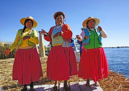 UROS ISLANDS, PERU - June 25, 2019 - Uros women on one of the Uros Islands near Puno, Peru. The islands are man-made of clay and totoro reeds and float on Lake Titicaca near the Bolivian border.