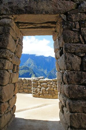 View of the Andes Mountains through a doorway at Machu Picchu