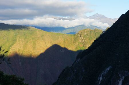 The sun breaks over the mountains and shines its first light on Machu Picchu mountain