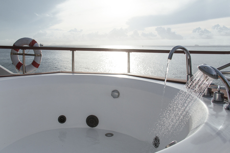 White bathtub in boat on morning sky background.
