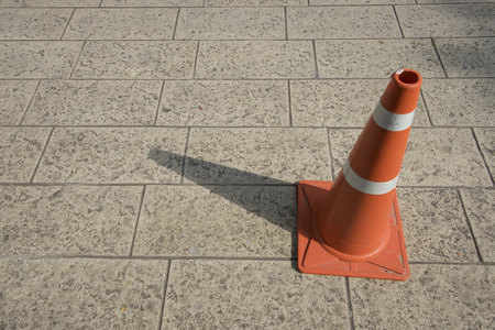 Orange traffic cone on pavement. Light and shadow on traffic cone. 스톡 콘텐츠