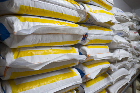 Pile of sack in warehouse. Background and texture of sack stack in warehouse. Standard-Bild