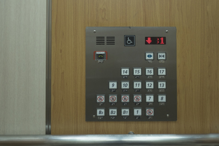 Close up of control elevator buttons for disabled human on wooden wallpaper.