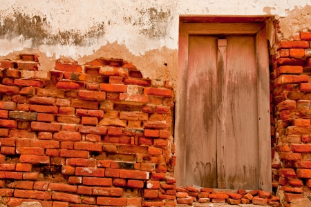 ancient wall with old door of buddhist church in thailand Stock Photo