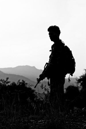 soldier with firearm in black white