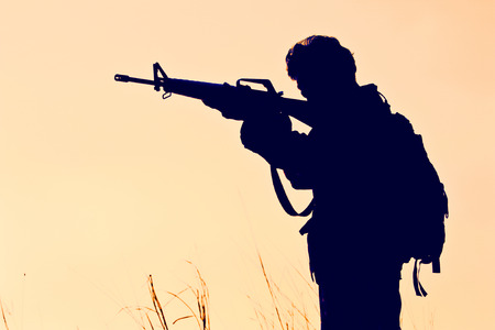 soldier with firearm in silhouette Stock Photo