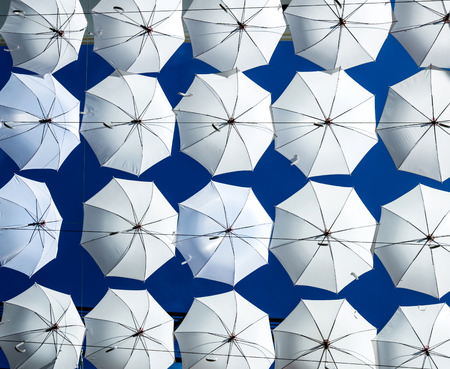 fall protection: a group of  white umbrella  on bright blue sky