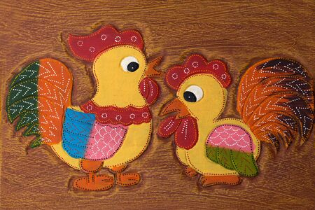 carve: wood carve of colorful chicken on top of teble