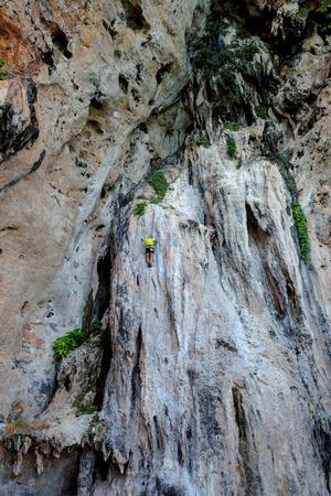 strong  man is blimbing cliff at Krabi, Thailand Stock Photo