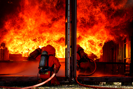 Feuerwehrleute sind mit Feuer Feuer Standard-Bild - 95022713