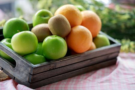 Many green apples , oranges and kiwi in wood box 免版税图像