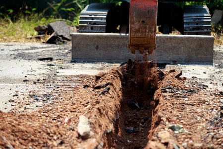 Backhoe is digging road to lay water pipe. 免版税图像 - 121005666