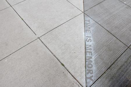 sprayed: TIME IS MEMORY sprayed painted on sidewalk