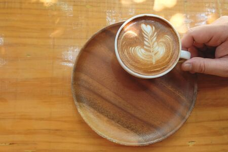 A cup of hot latte art holding by hand in wooden tray on wooden table with the light