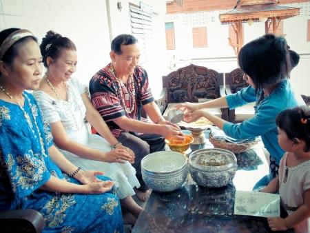 尊敬される年長者の手に水を注ぐし、Songkarn 祭での祝福を求める