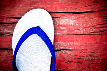 A casual one side slipper on wood red floor photo