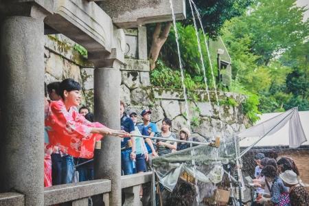 京都の清水寺の音羽の滝の滝から水を集める人 報道画像