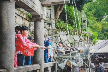 people collecting water from the Otowa-no-taki waterfall at Kiyomizu temple in Kyoto